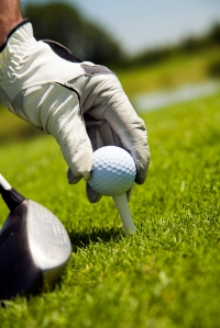 Golf club: golfer arranging the ball on the tee